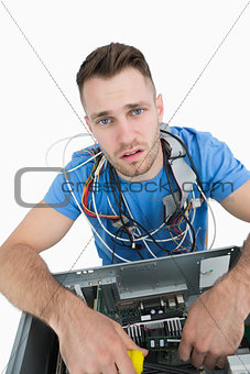 Portrait of tired it professional with cables around neck
