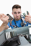 Portrait of confused it professional with chips in front of open cpu