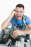 Frustrated computer engineer screaming over the phone in front of open cpu