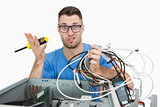 Portrait of confused it professional with screw driver and cables in front of open cpu