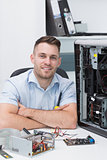 Smiling hardware professional sitting by an open cpu