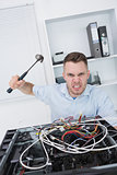 Portrait of frustrated man hitting cpu with hammer