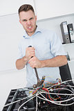 Portrait of frustrated man using hammer to pull out wires from cpu