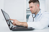 Hardware professional examining laptop with stethoscope