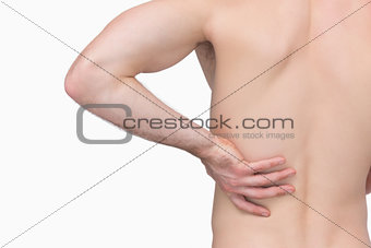 Rear view of shirtless man with hand on hip