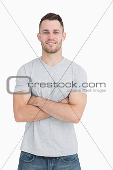 Portrait of casual young man standing with arms crossed