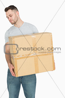 Young casual man carrying cardboard box
