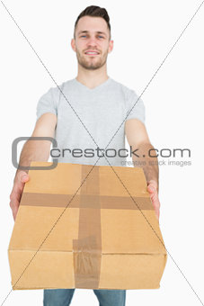Portrait of young man giving you a package box