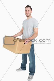 Portrait of young man carrying cardboard box