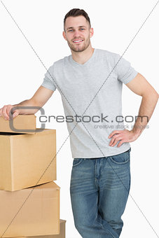 Portrait of smiling young man with cardboard boxes