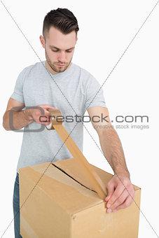 Man sealing cardboard box with packing tape