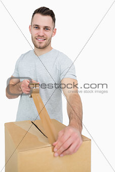 Portrait of man sealing cardboard box with packing tape