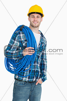 Portrait of smiling male architect carrying coiled blue tubing