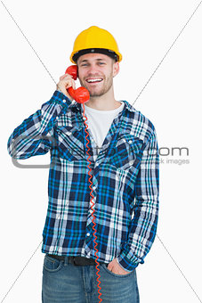 Portrait of young male architect using landline phone