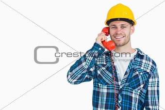 Portrait of male architect using landline phone