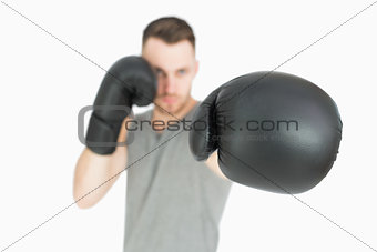 Portrait of young male boxer punching