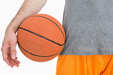 Closeup midsection of man with basketball