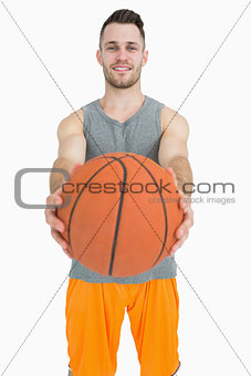 Portrait of happy young man holding basketball