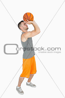 Side view of a young man throwing basketball