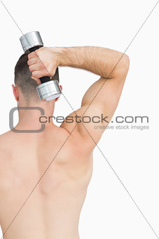 Rear view of man exercising with dumbbell