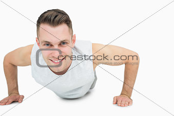 Portrait of smiling young man doing push ups