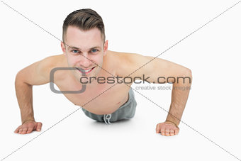 Portrait of happy shirtless man doing push ups