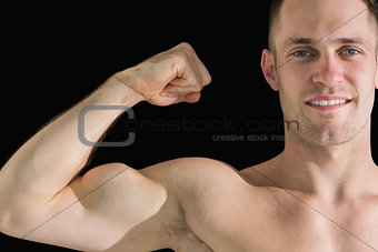 Closeup portrait of young man flexing muscles