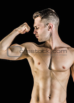 Shirtless young man flexing muscles
