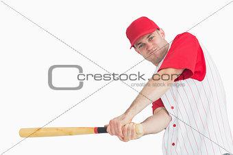 Portrait of young baseball player swinging bat