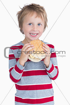 Cute happy young boy holding burger