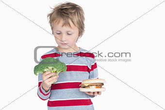 Young boy holding broccoli and burger