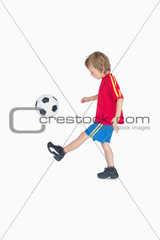 Side view of little boy kicking football