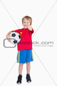 Portrait of boy with football gesturing thumbs up