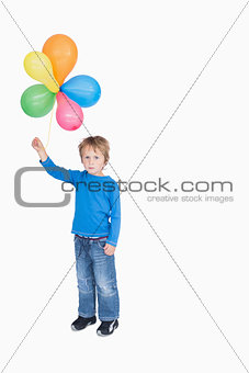 Portrait of young boy holding a bundle of balloons