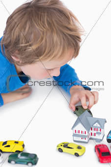Closeup of boy playing with playhouse and toy cars