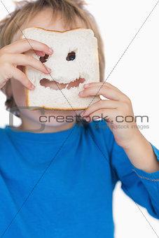 Boy looking through holes in bread slice