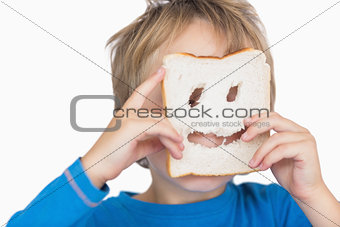 Young boy looking through holes in bread slice