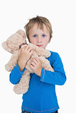 Portrait of cute young boy hugging teddy bear