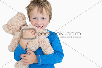 Portrait of happy young boy hugging teddy bear