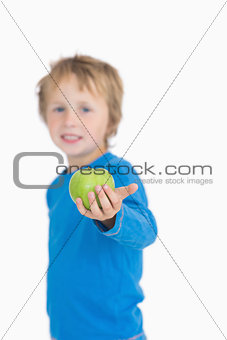 Portrait of young boy holding out a green apple