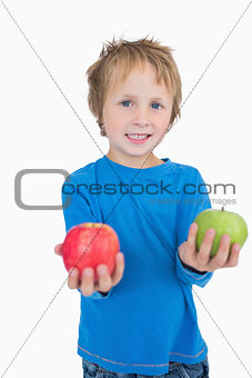 Portrait of boy holding out green and red apples