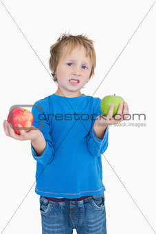 Portrait of young boy holding out green and red apples