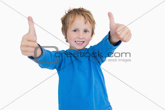 Portrait of young boy gesturing double thumbs up