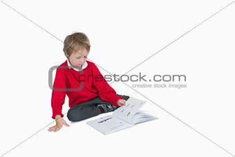 Little boy sitting and reading book