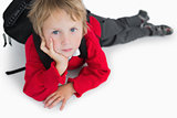 Boy lying on floor with schoolbag