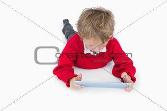 Little boy lying on floor and using digital tablet