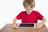 Little boy sitting at desk and looking at digital tablet