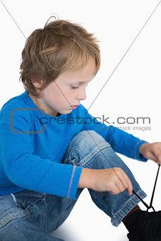 Little boy binding laces