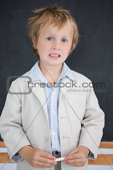 Boy dressed as teacher in front of black board