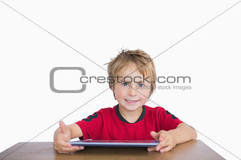 Portrait of little boy sitting at desk with digital tablet